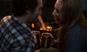 couple sharing hot chocolate at camping engagement