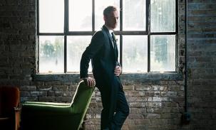 groom-posing-by-glass-windows