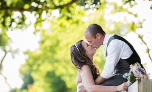 bride-and-groom-kiss-on-fence